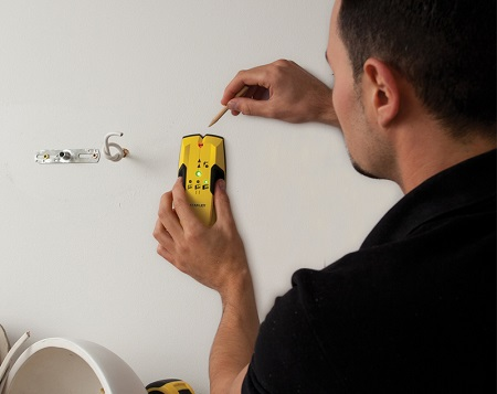 Man using a Stanley stud finder.